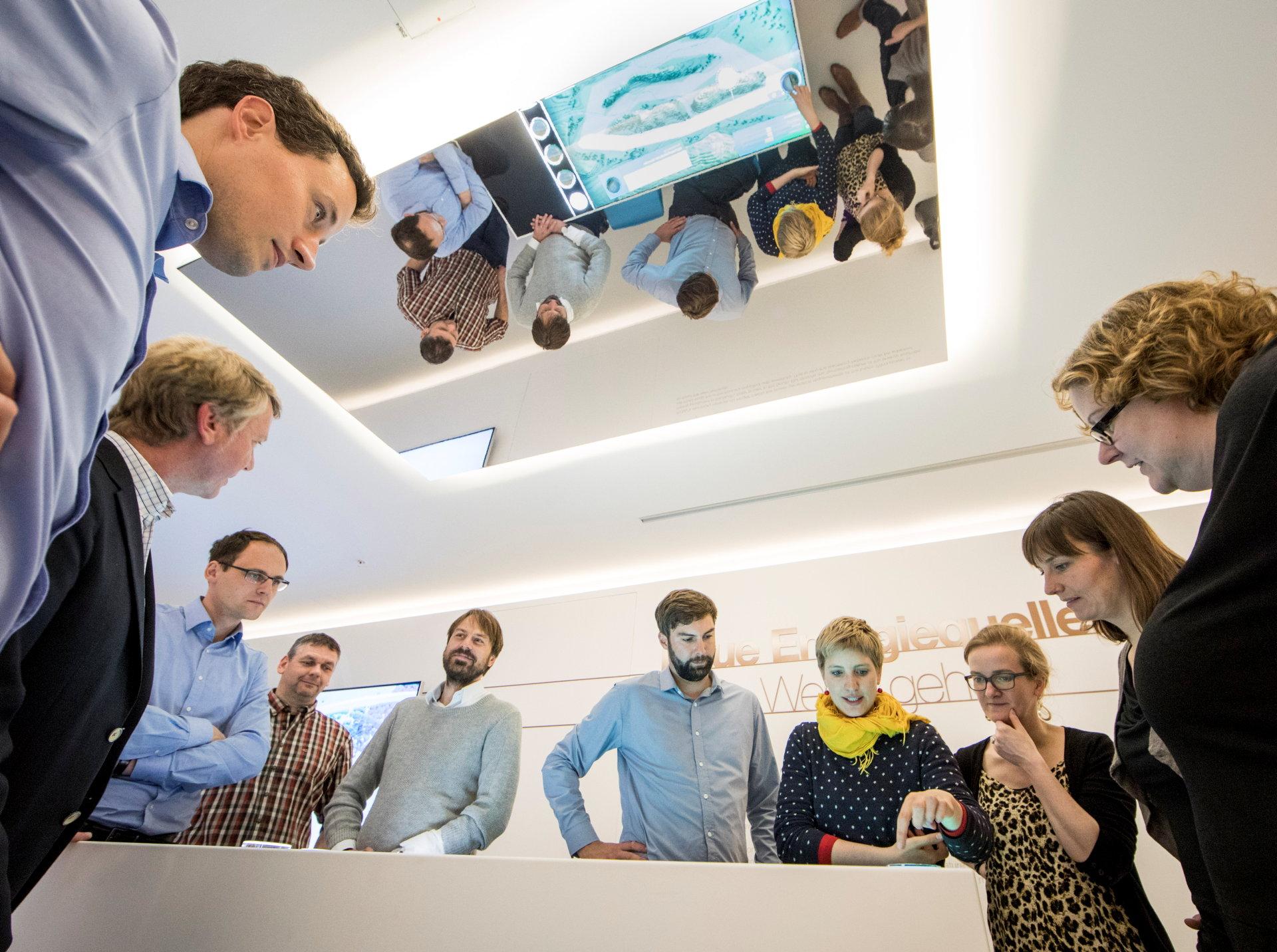 Menschen schauen auf  einen Tisch mit einem Planspiel zum Stromtrassenbau.