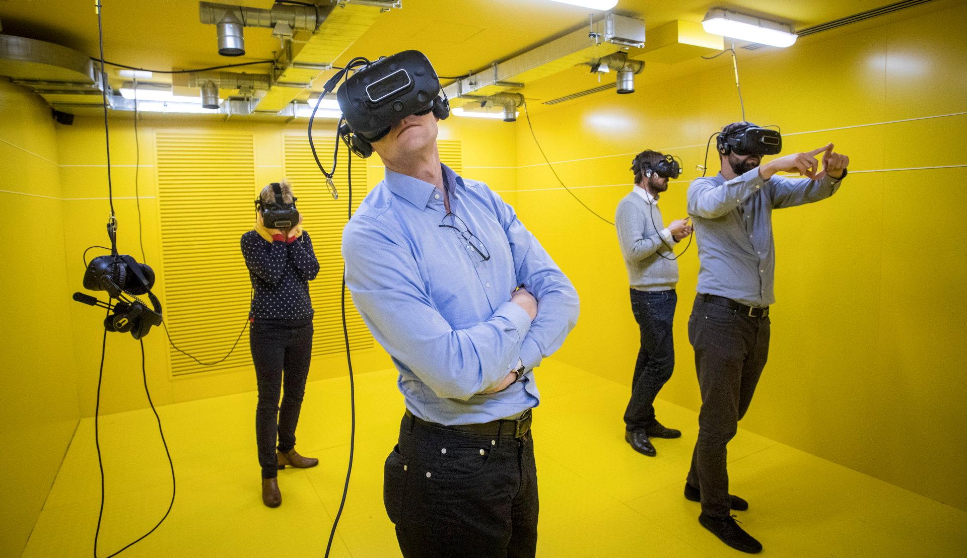 Vier Personen stehen in einem vollständig gelben Raum mit Virtual-Reality-Brillen auf dem Kopf.