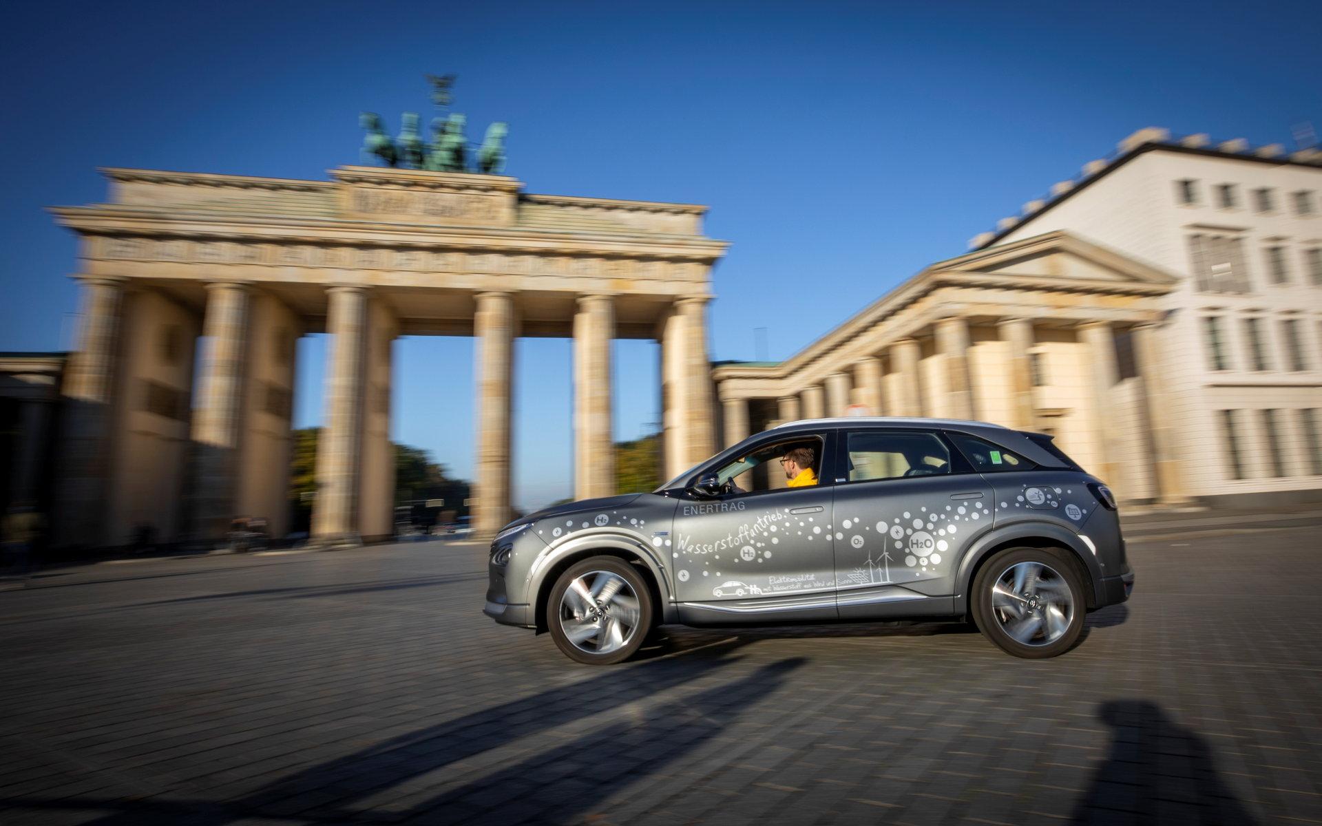 Graues Auto vor Brandenburger Tor in Berlin.