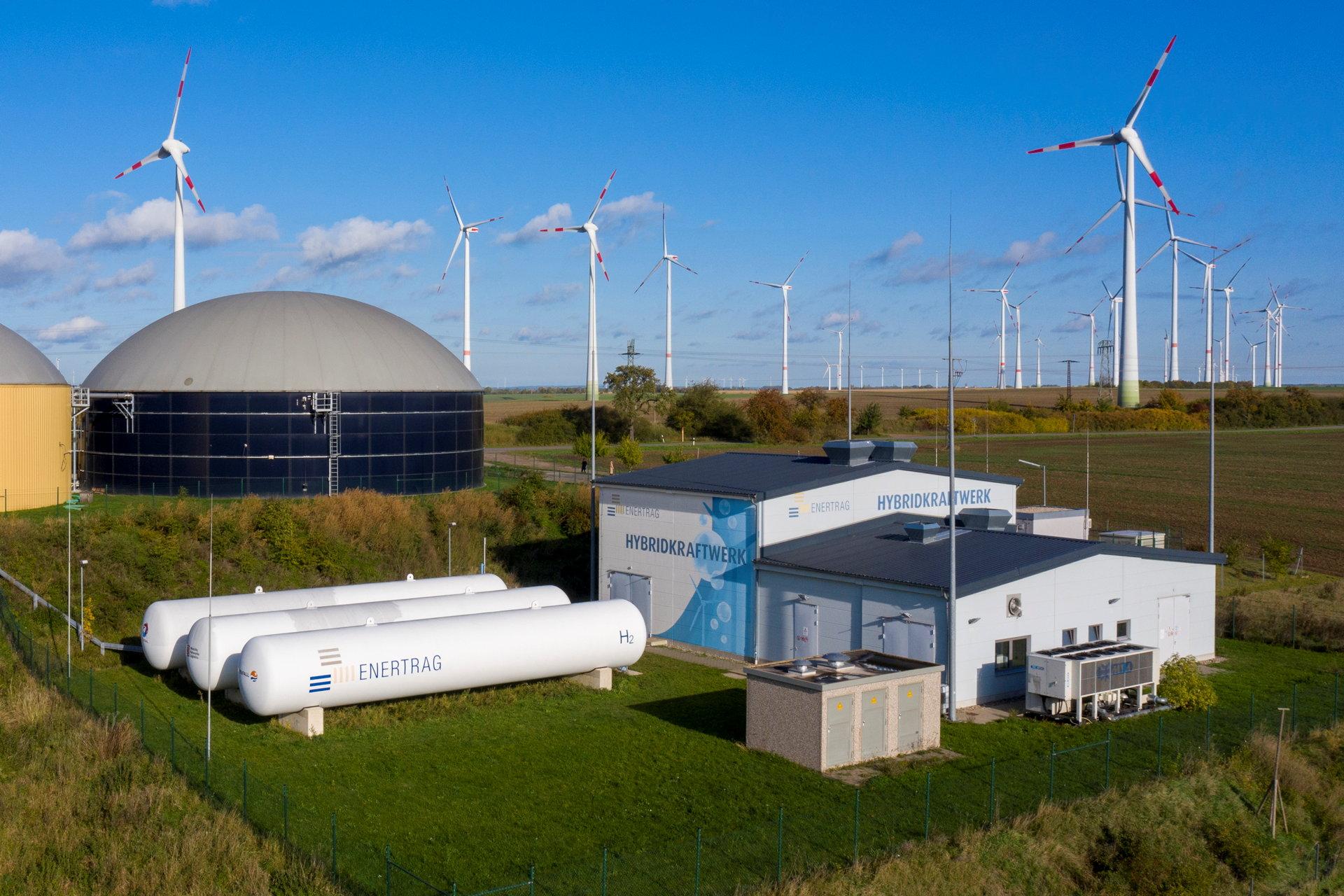 Kraftwerksgebäude mit drei weißen, zylindrischen Tanks und Biogasfermenter.