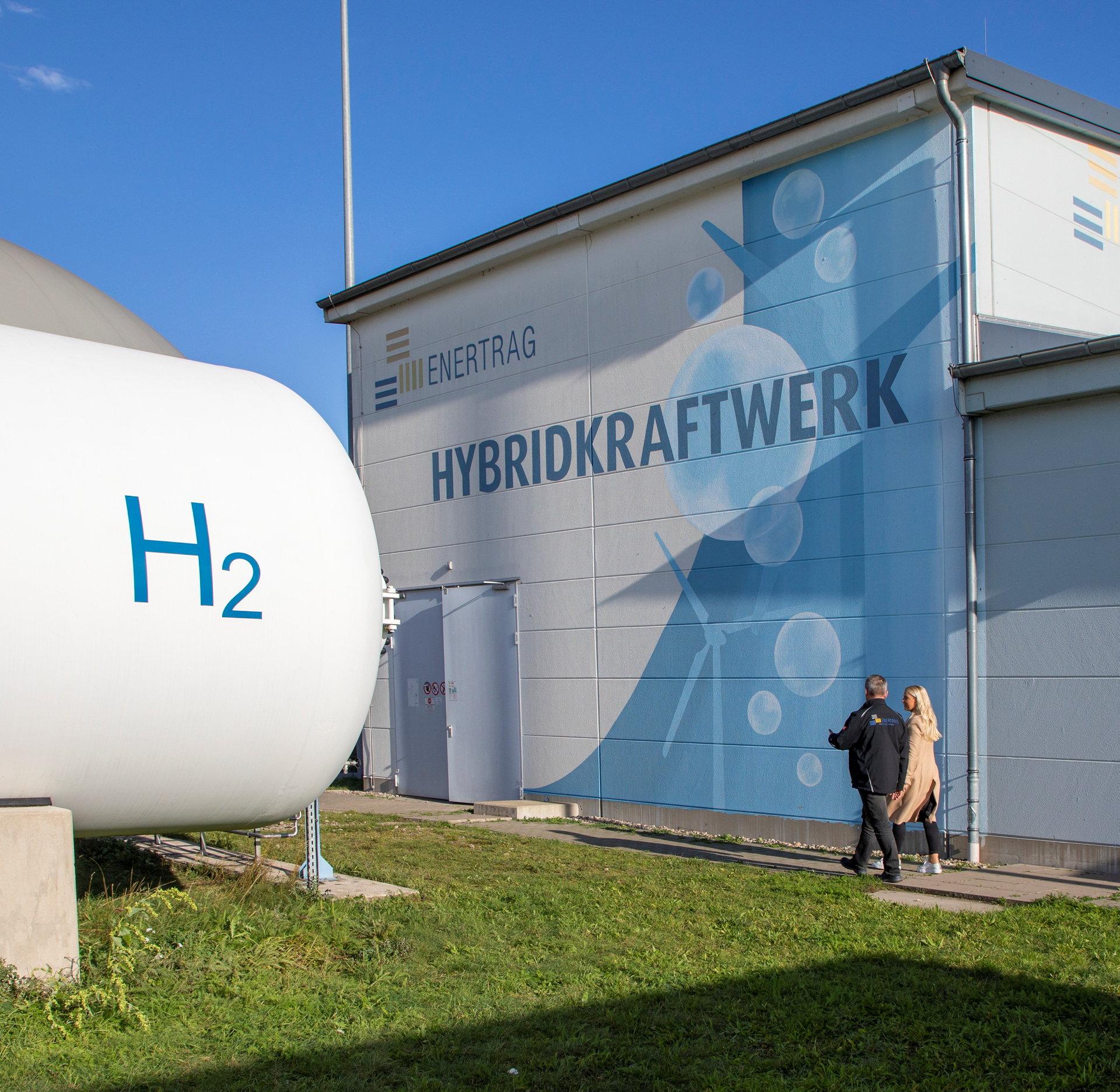 Weißer Wasserstofftank und Hybridkraftwerksgebäude von außen.