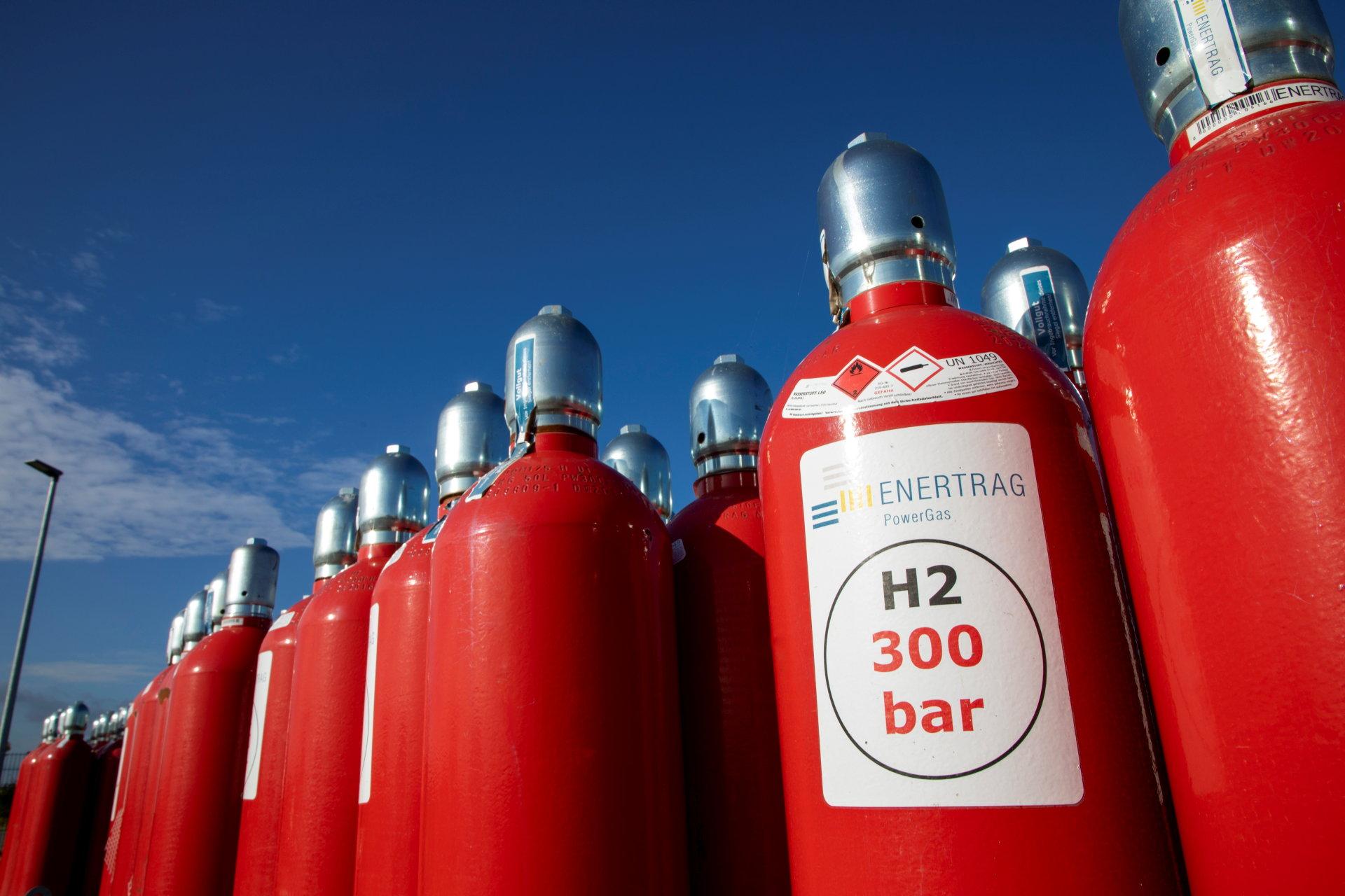 rote Wasserstofflaschen vor blauem Himmel