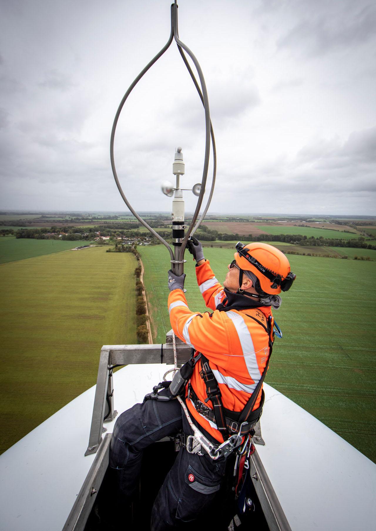 Monteur sitzt auf Windkraftanlage und guckt auf Anemometer.