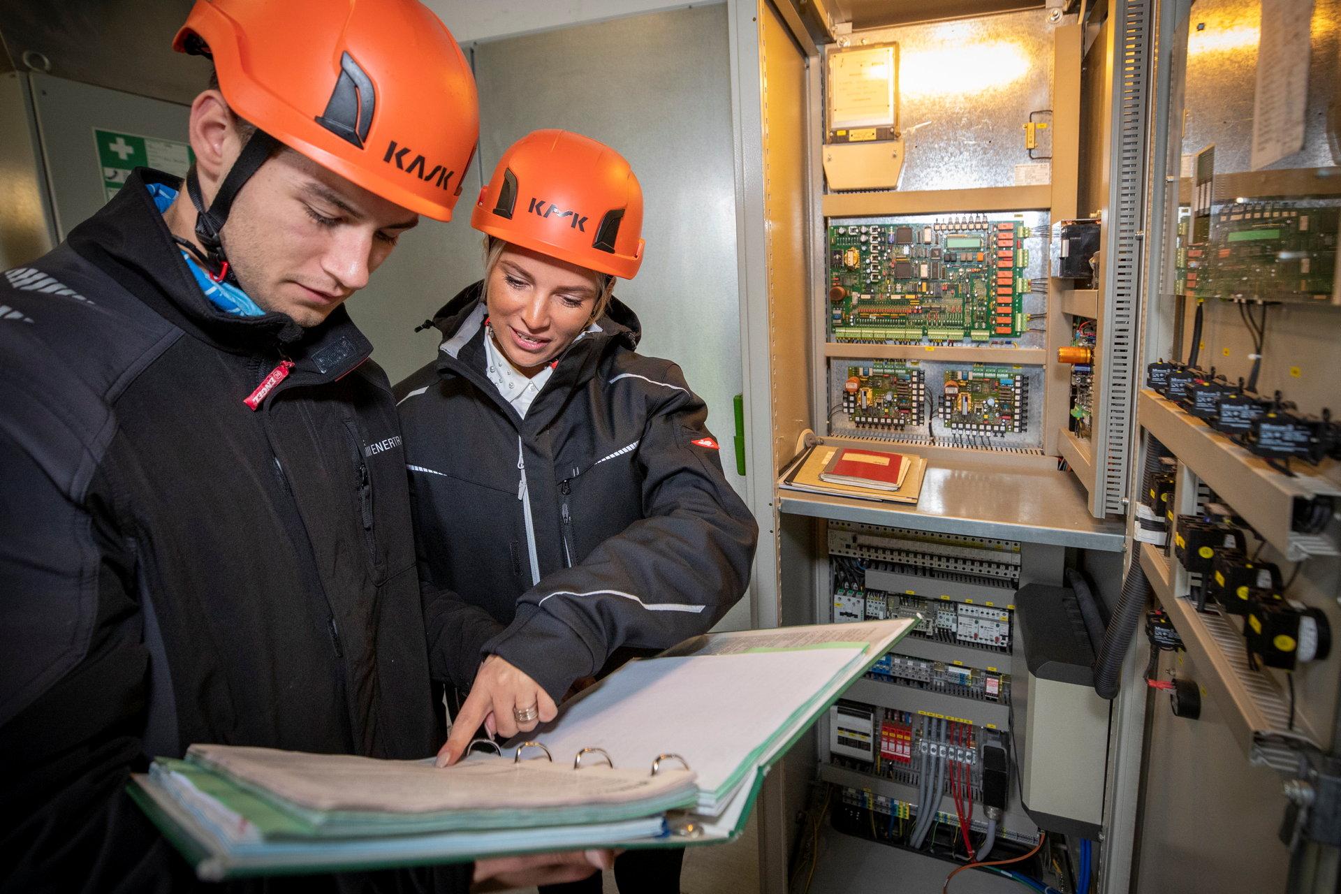 Zwei junge Monteure schauen in einen Ordner vor Schaltschrank in Windkraftanlage.