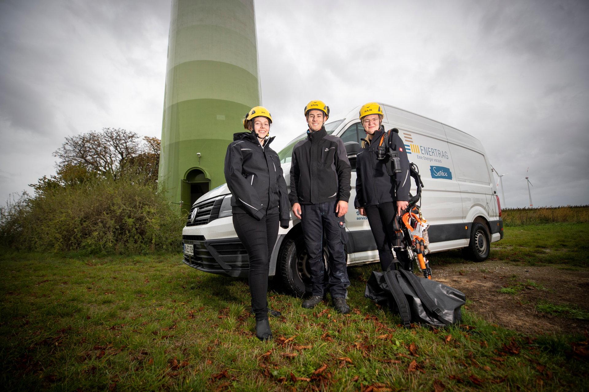 Drei Auszubildende mit orangenen Schutzhelmen vor Auto und Windkraftanlage.