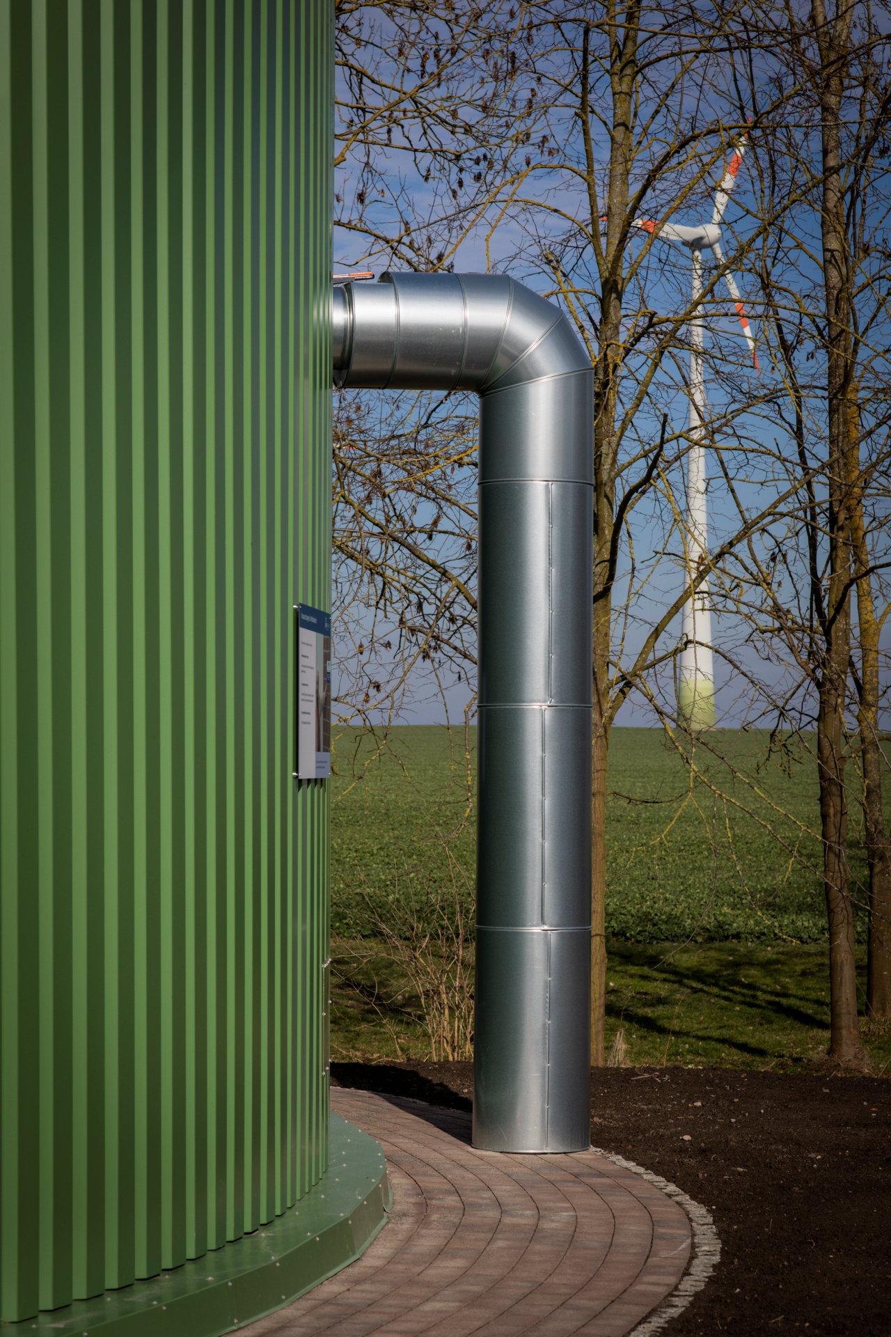 Ein Rohr führt vom Boden in einen großen grünen Tank, Im Hintergrund steht eine Windkraftanlage.
