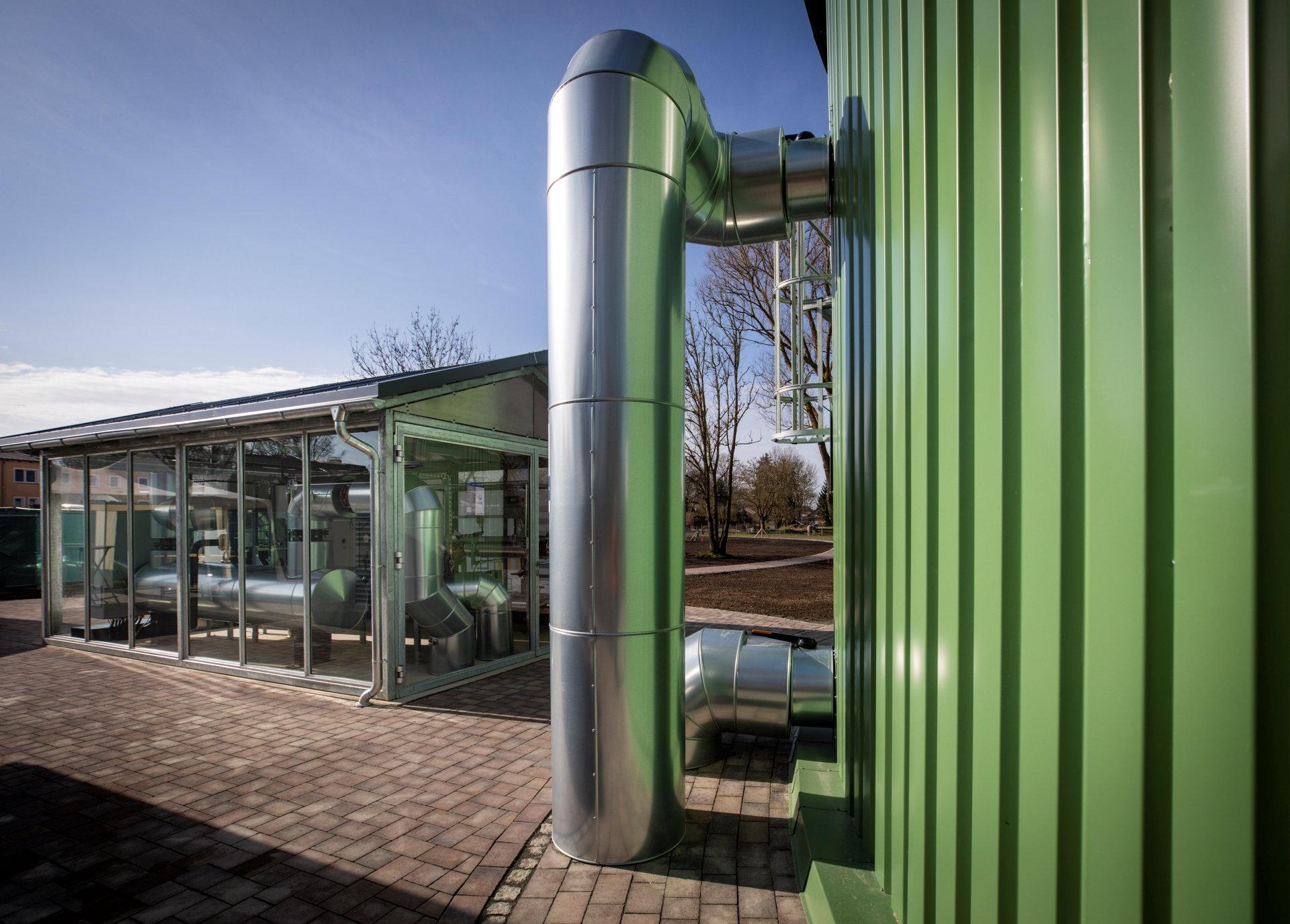 Ein dickes Rohr führt vom Boden in einen grünen Silo.