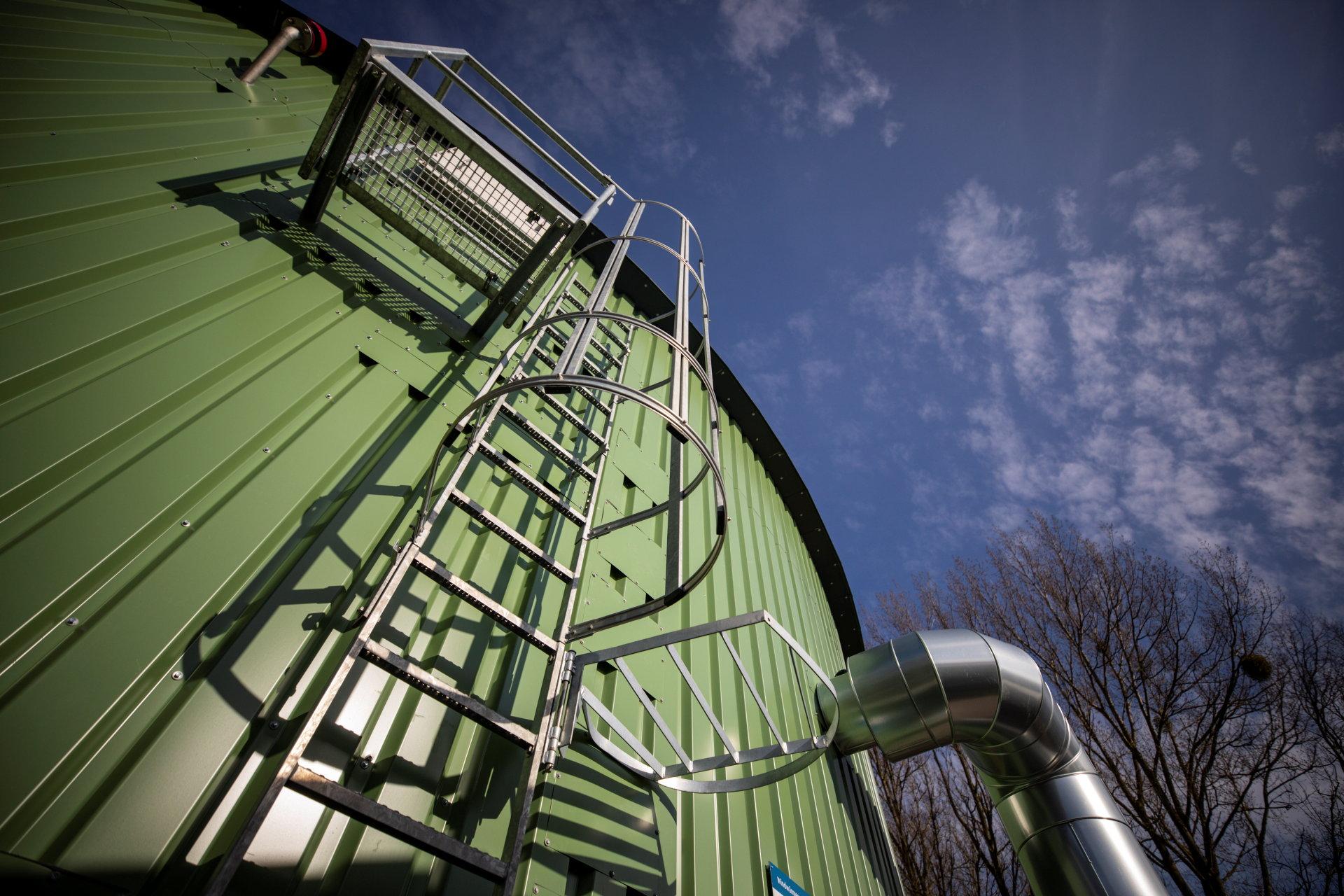 Eine Leiter führt an einem grünen zylindrischen Silo nach oben.