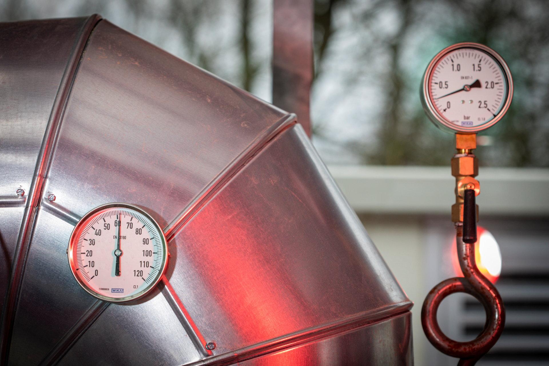 Dicke blanke Rohre mit zwei Armaturen für Temperatur und Druck.