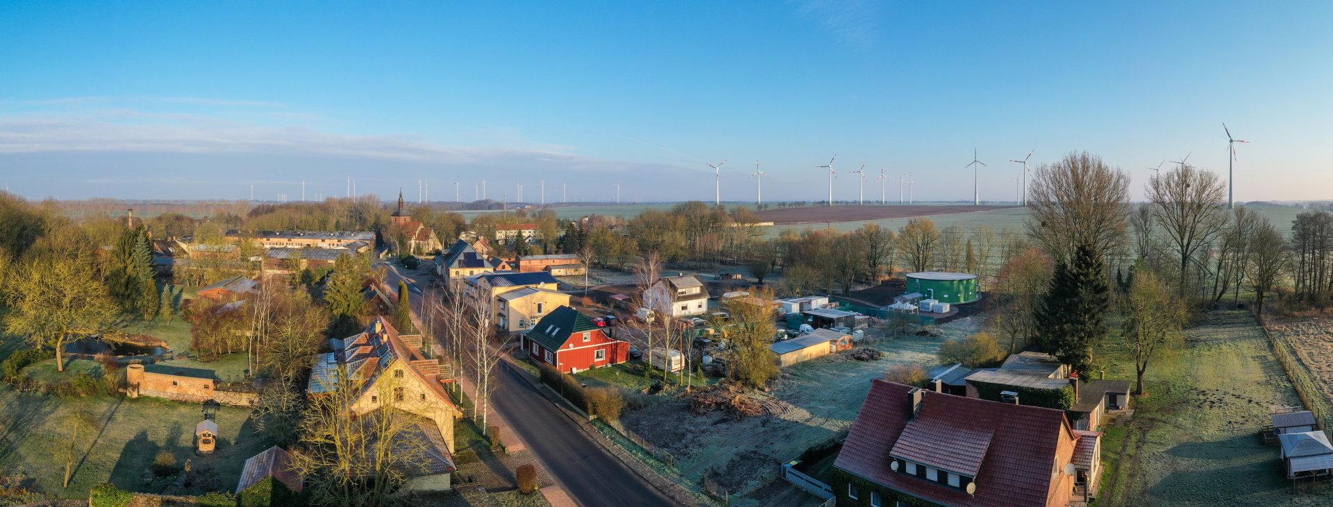 Ein Dorf mit Einfamilienhäusern entlang einer Straße von oben aufgenommen, im Hintergrund stehen Windkraftanlagen auf dem Feld.