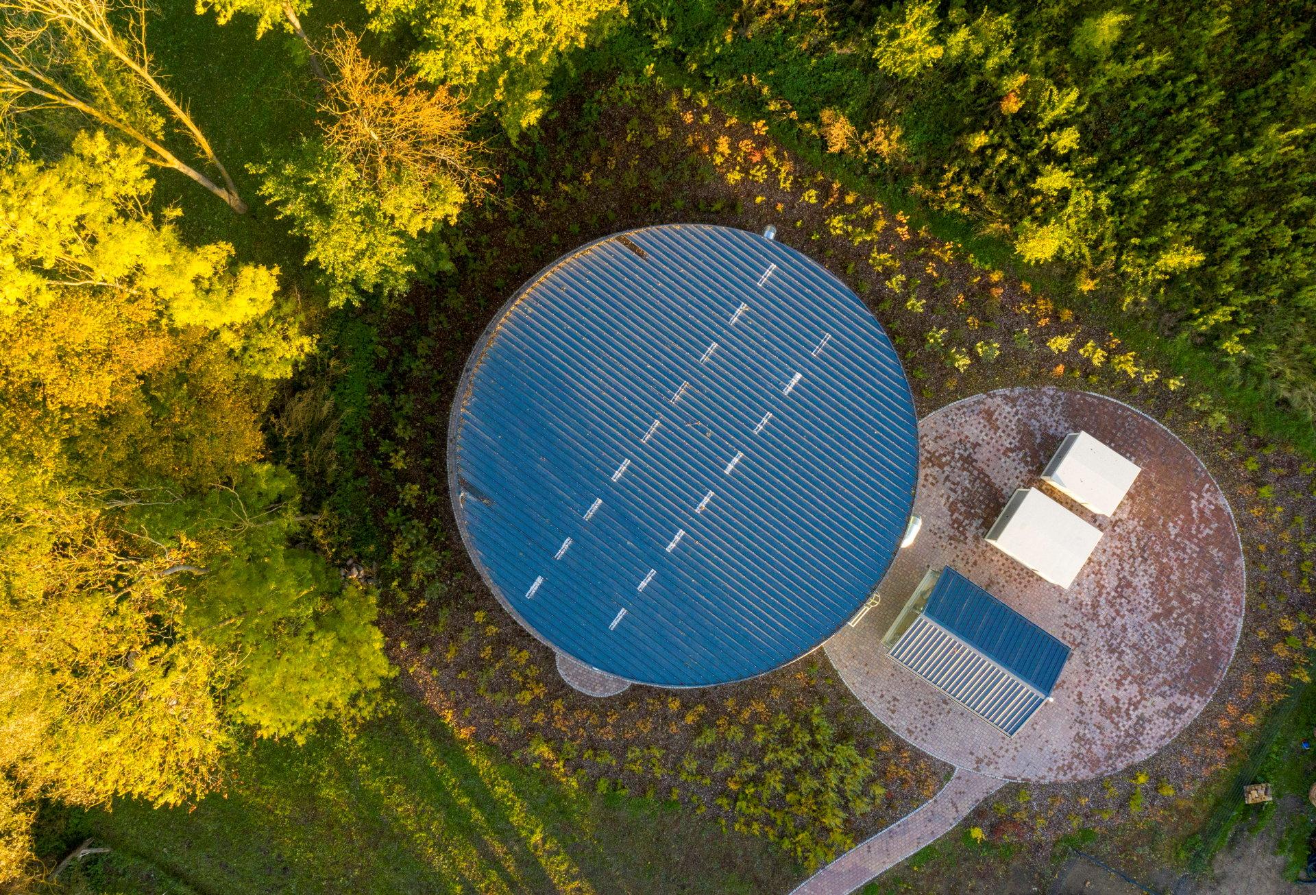 Ein kreisförmiger Silo mit blauem Dach und drei kleinen rechteckigen Gebäuden daneben von oben betrachtet.