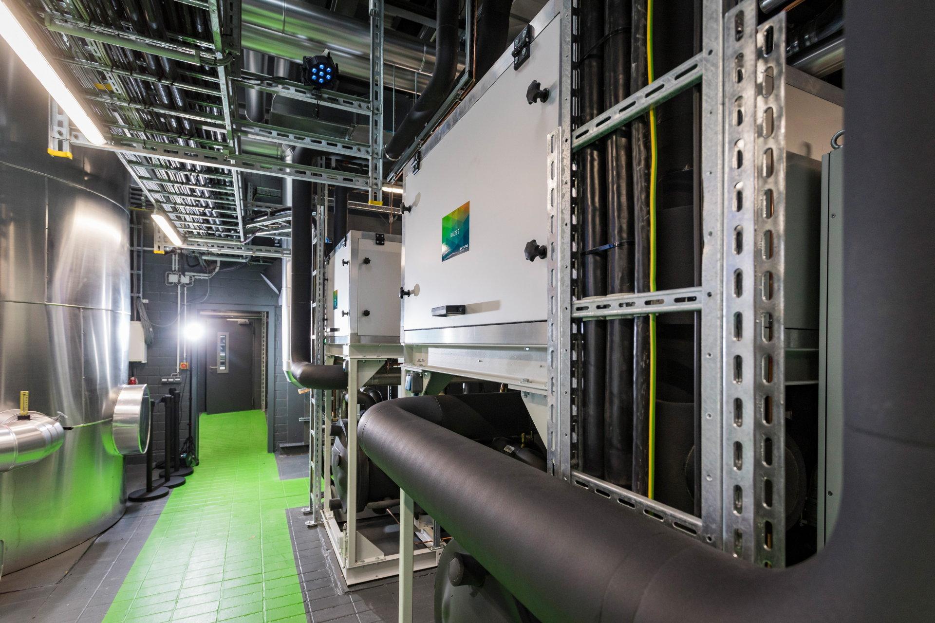 Schwarz ummanteltes Rohr führt durch eine Maschinenhalle