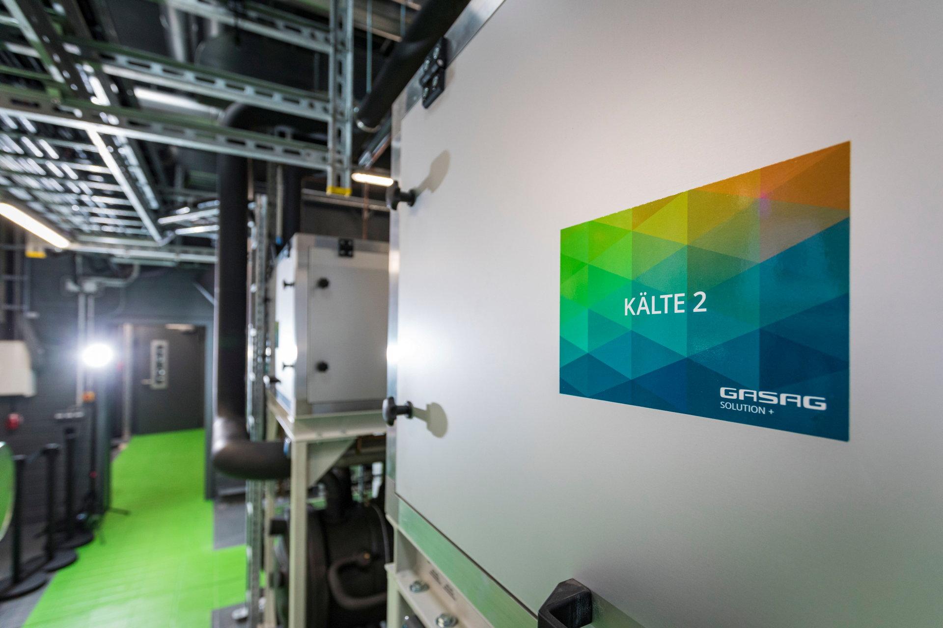 Schild mit Beschriftung Kälte 2 auf einem grauen, großen Schrank in Maschinenhalle