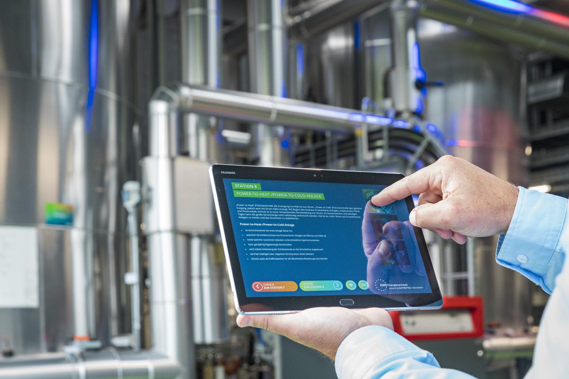 Tablet mit blauem Erklärungsbild für Energiezentrale, Hintergrund Maschinenhaus