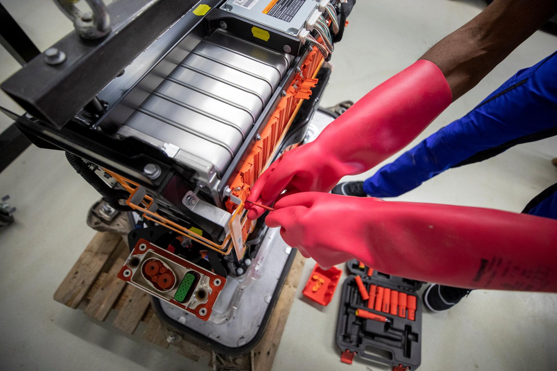 Mit roten Sicherheitshandschuhen an Batterie schrauben