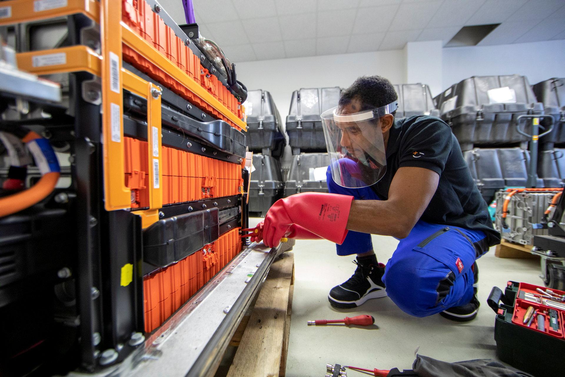 Mann mit roten Handschuhen schraubt an Batterie