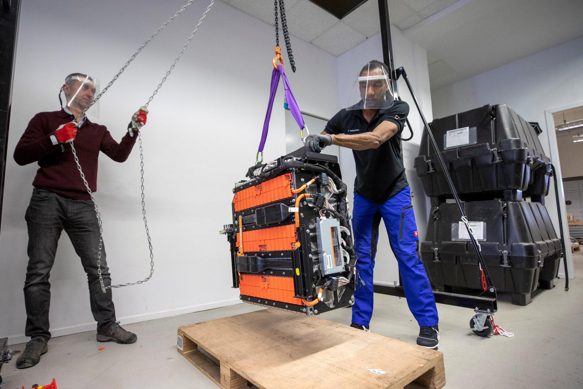 Gebrauchte Elektroautobatterie wird von zwei Männern umgesetzt.