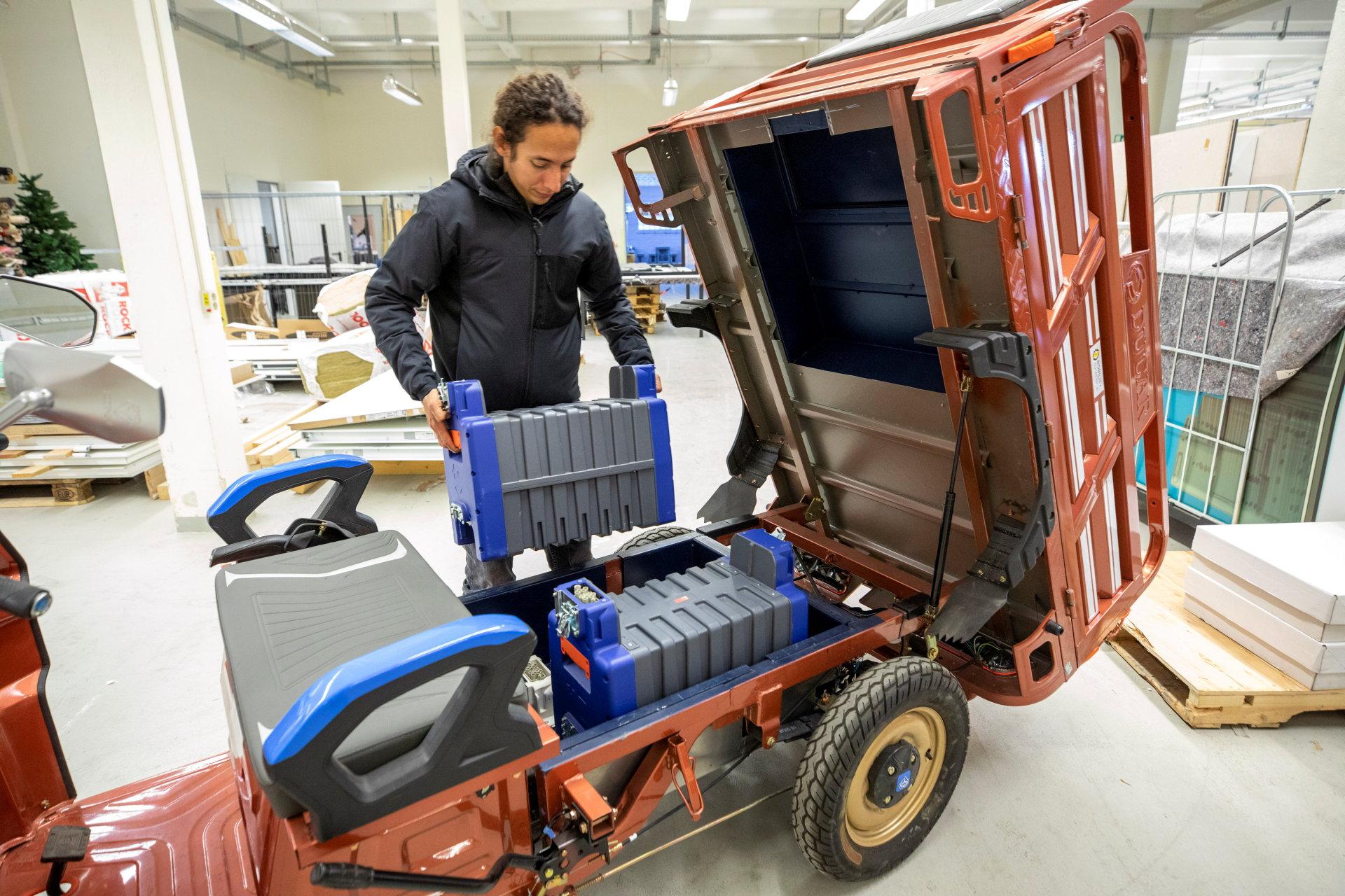 Mann hievt große Batterie aus Kleinfahrzeug