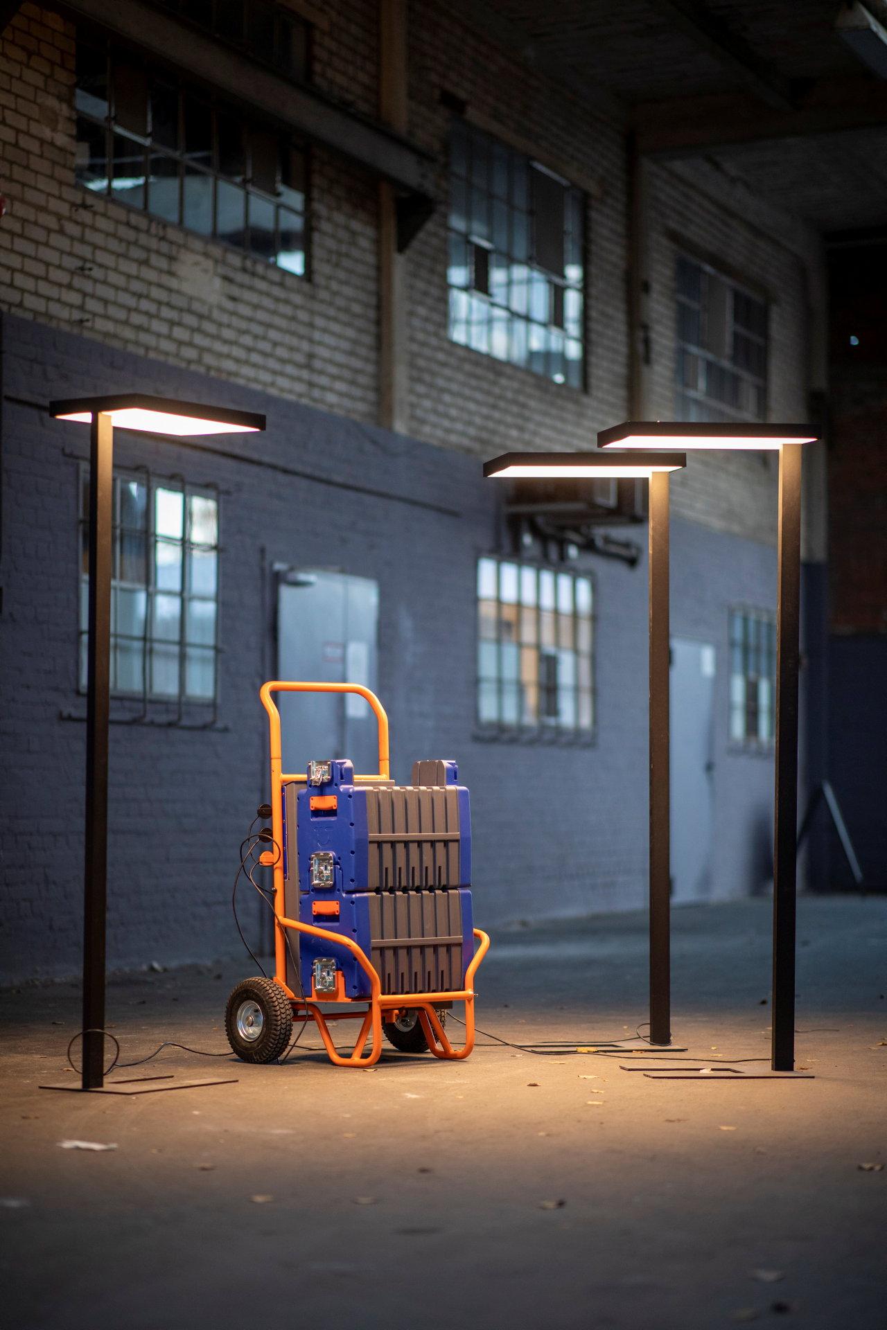 Sackkarre mit großen Batterien von drei Lampen beleuchtet.