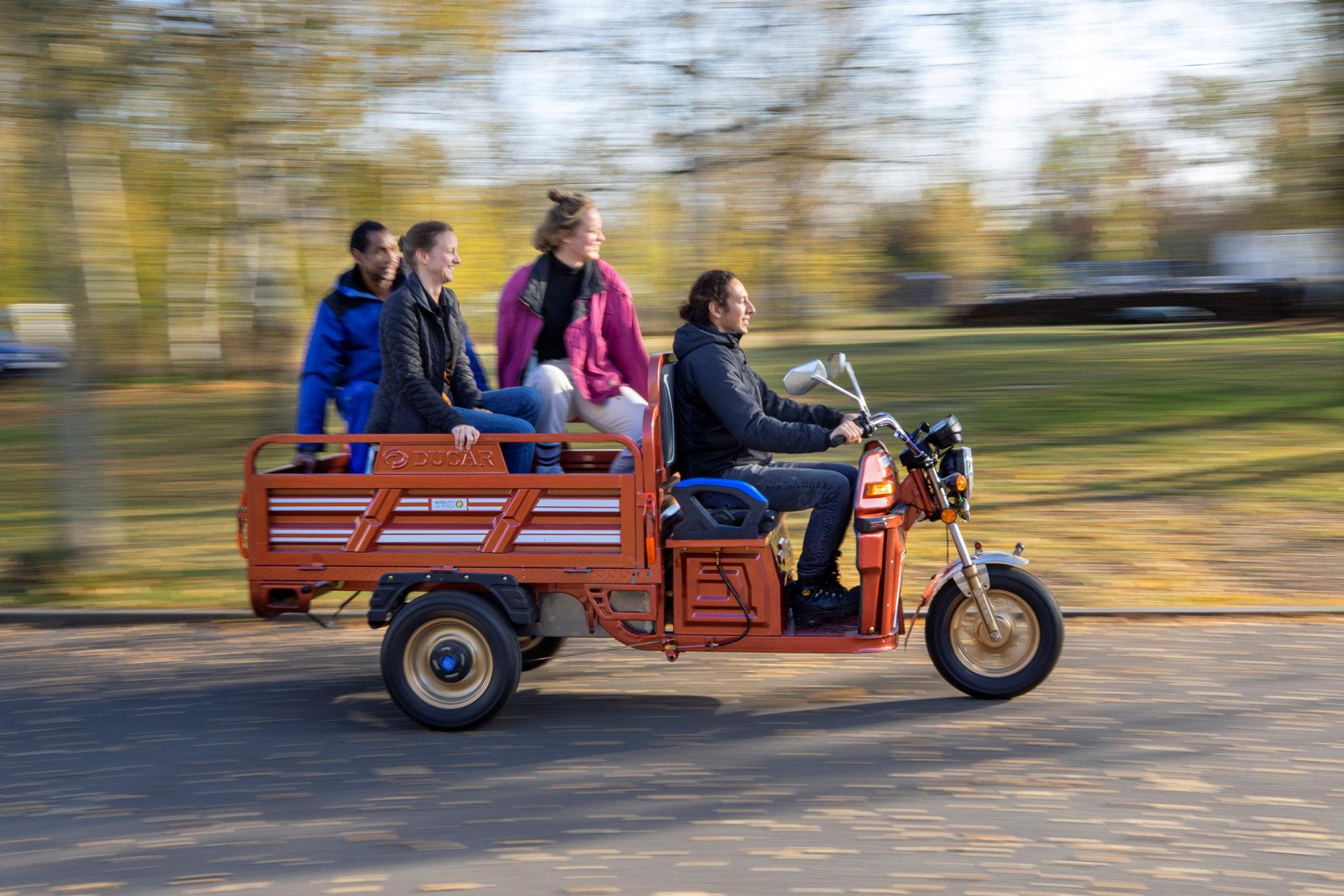 Vier Personen auf rotem, dreirädrigem Kleinfahrzeug.